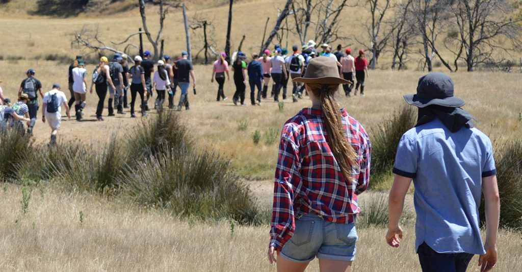 Two Young Rural Leaders program participants walk together through grass.