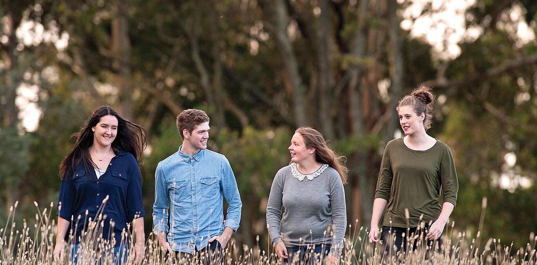 4 Youthrive Scholars walking through tall grass, having a conversation.