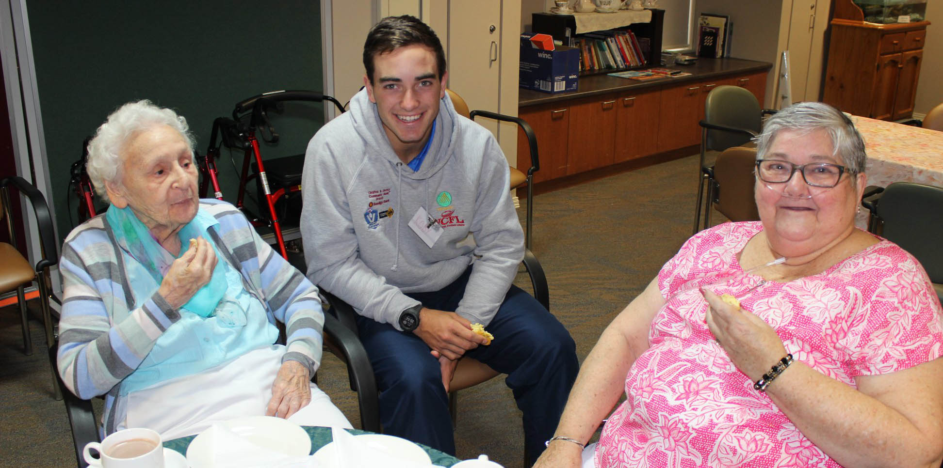 Youth leadership program participant talking to elders at nursing home.