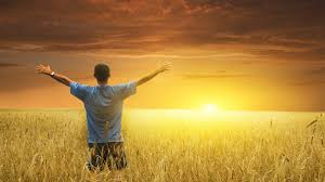 Man looking towards sunset with his hands in the air.